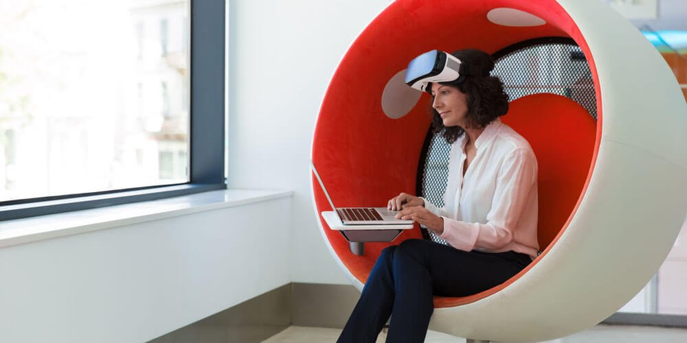 Frau mit VR-Brille und Laptop